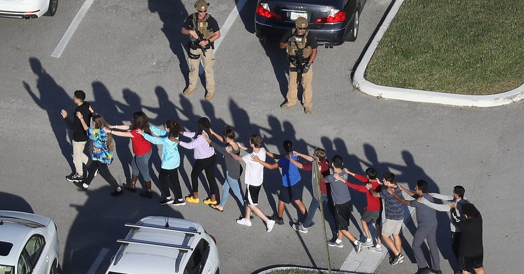 Students walk outside the school with hands on eachothers shoulders showing they are not a threat. The Millitary and police evacuated the building as quick as possible.