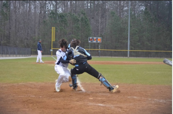 Lafayette high school Junior, Thomas McLaughlin collides with Warhill catcher Junior, Riley Motley at a close play at the plate.