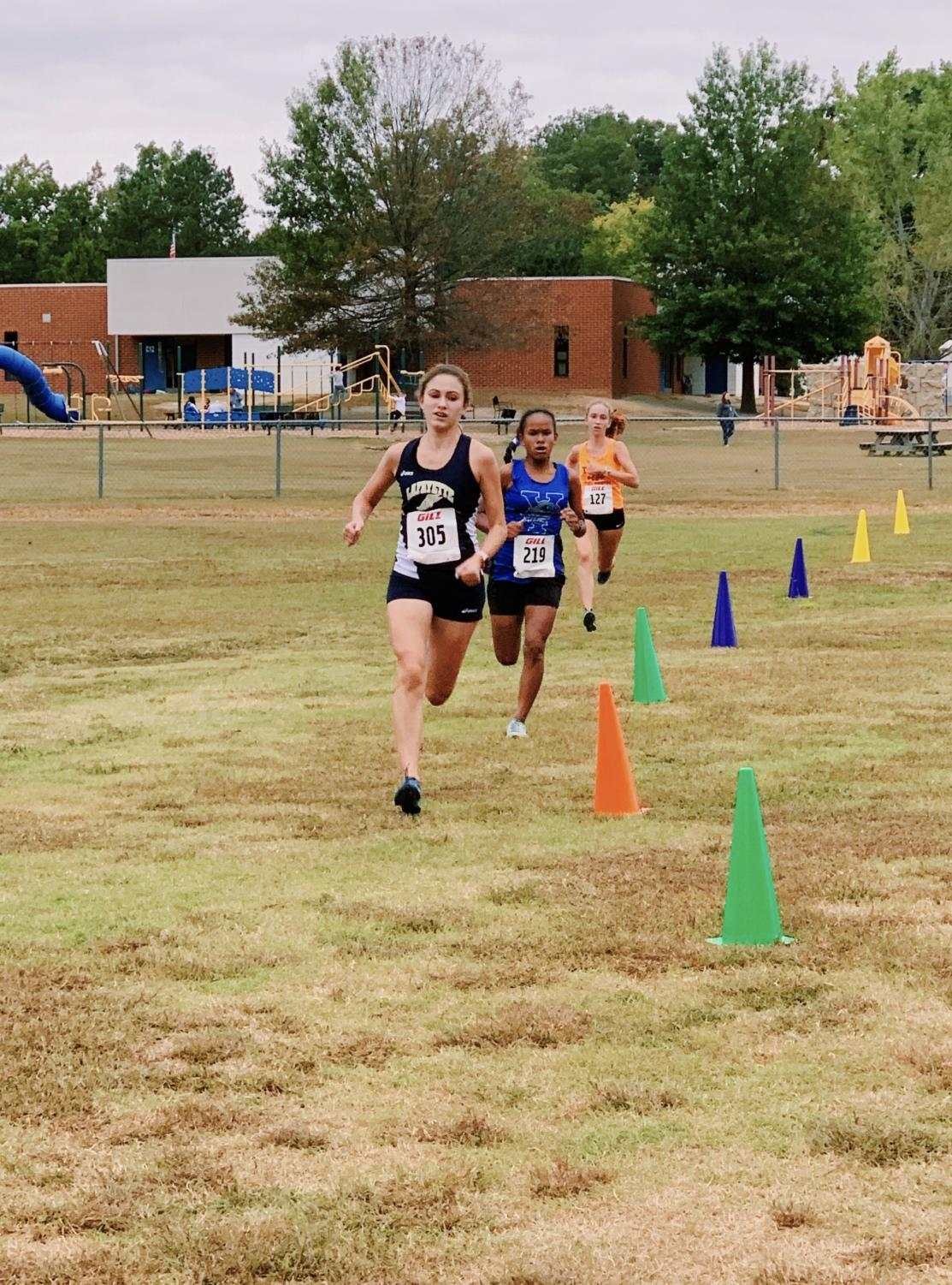 Senior Captain, Allison Crookston finishes strong at the end of the long race. A York runner tries to beat Allison in the final stretch, but Allison was able to out kick her.
