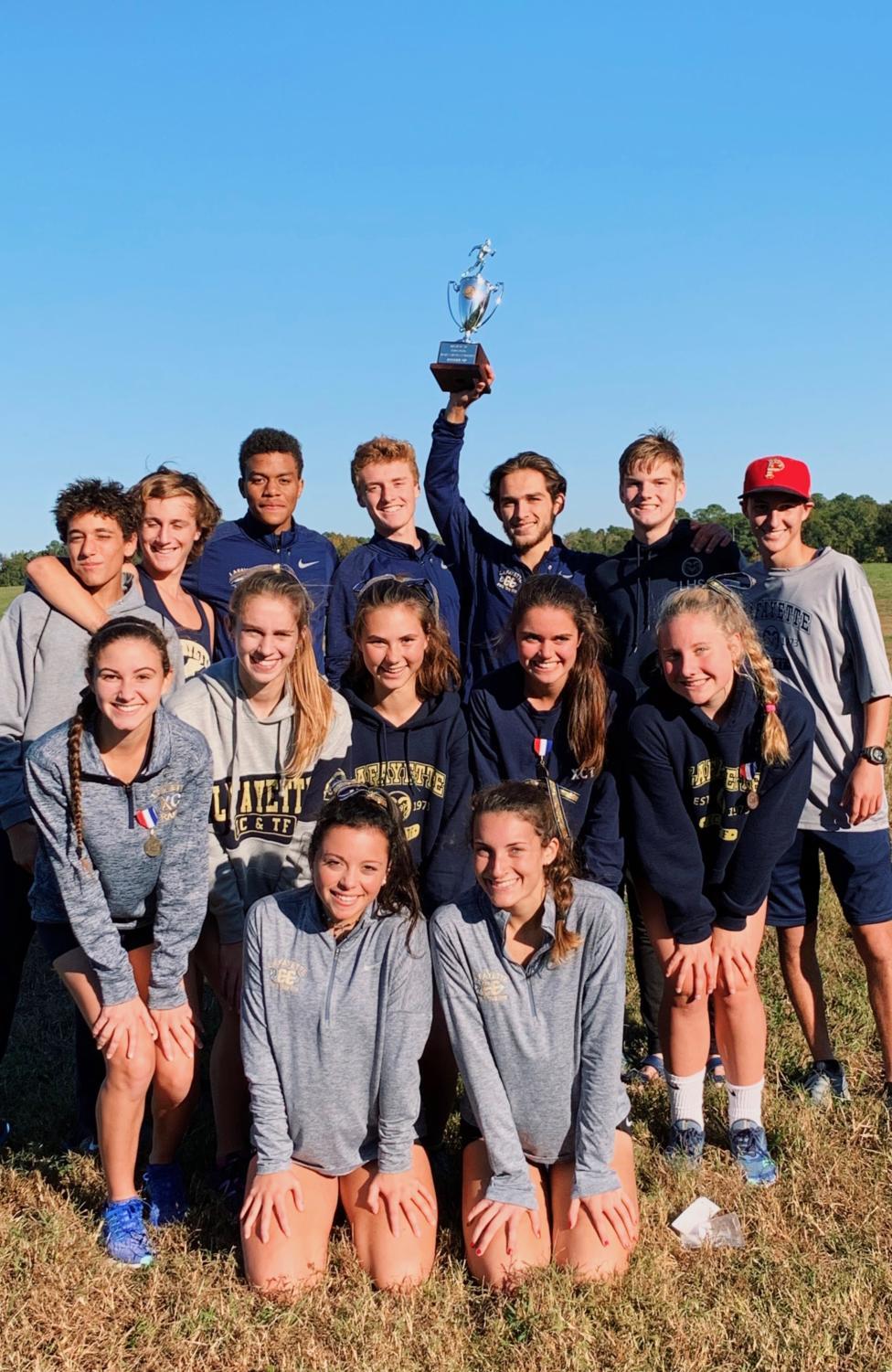 The boys and girls Lafayette Cross Country team pose together after Regionals. Zachary Barbarji holds up the boys' second place trophy.