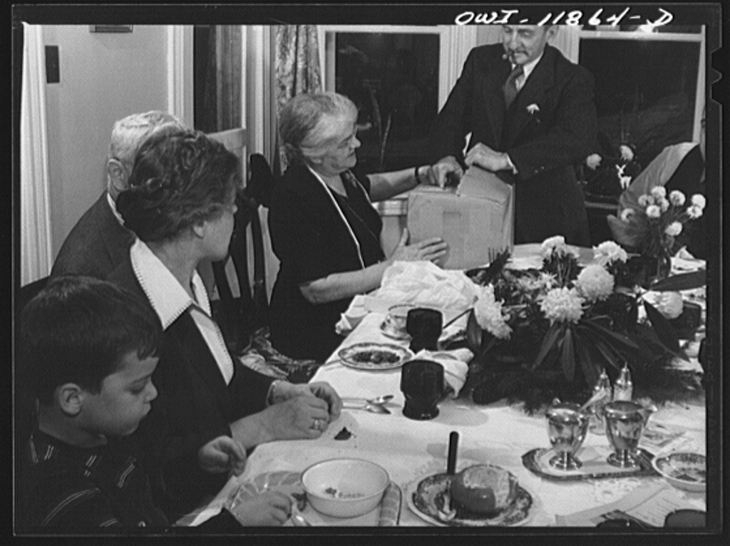 Families join together to eat dinner on Thanksgiving.