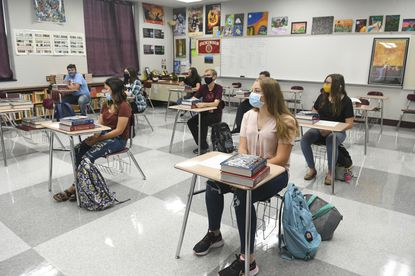 Students sit in class wearing their masks and with their desks spaced away from eachother.