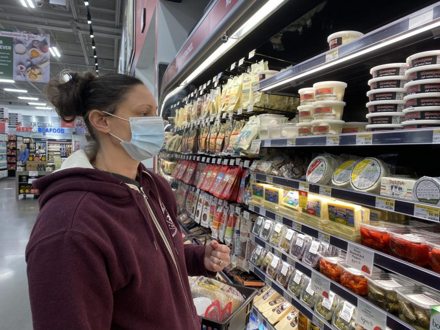 Outside of Earth Fare, a well established grocery store, there's a sign saying all customers and employees must enter the building with a mask or some sort of facial covering. Here my mom and I are looking at different cheeses to buy. Around us, everyone was wearing a mask.